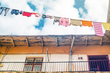 Linen Is Dried On Clothesline On A Background Of Blue Sky With Clouds. Sunny Day In The Yard-Well. Old Building Facade