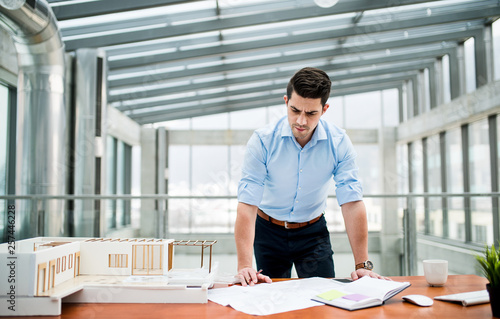 Foto auf Leinwand Akt Young businessman or architect with model of a house standing in office, working.