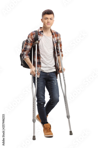 Photo Male student walking with crutches