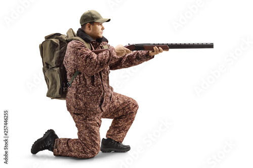 Photo  Man hunter in a uniform kneeling and aiming with a shotgun