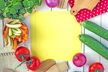 Culinary Background. The Light Wooden Surface On It Is A Yellow Lettering Sheet, Around Fresh Vegetables, Greens, Items For Cooking. Copy Space Top View