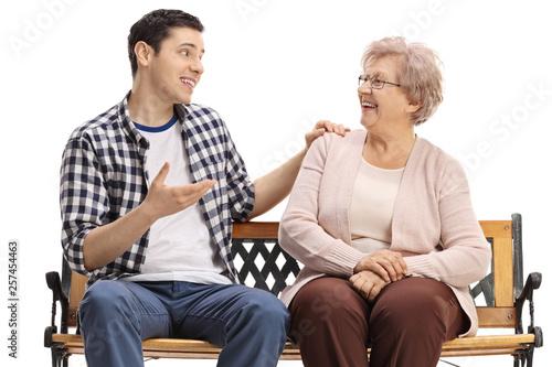 Young guy and a senior woman sitting on a bench and talking Tapéta, Fotótapéta