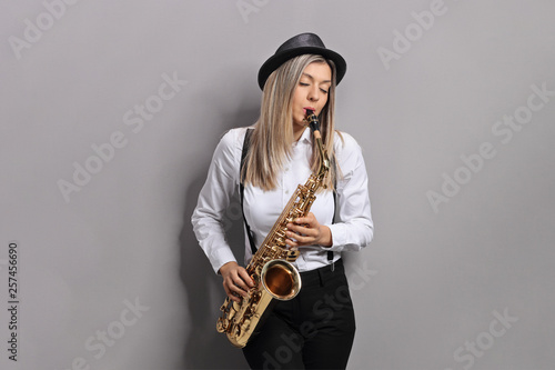 Obraz na plátně Young female musician playing saxophone and leaning against gray wall