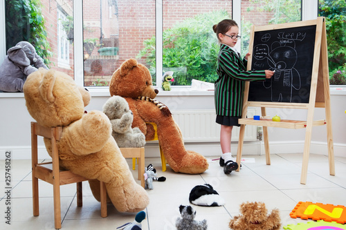 Young girl pretending to be a teacher to her teddy bears