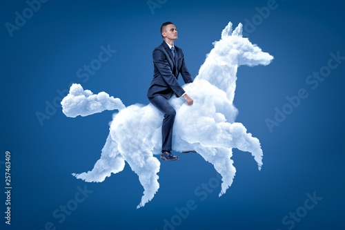 Obraz na płótnie Young businessman riding white cloud horse on blue background