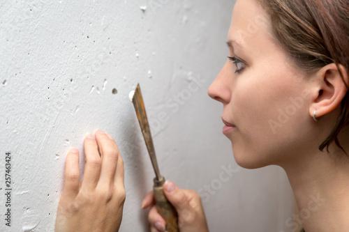 Fotografia, Obraz  Junge Frau renoviert ihr Eigenheim, Loch zuspachteln