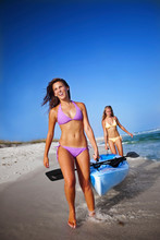 Two Girls Walk With A Sea Kayak Along Pensacola Beach, Florida.