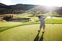 A Male Golfer Hitting A Golf Ball At Sunset