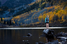 A Young Woman Hiking Stands On A Log And Takes In The View Of The Fall Colors And Maroon Lake.