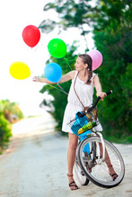 A Young Woman Riding A Bike On...