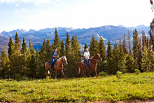 Couple Enjoying Horse Riding In The Meadow During Summer