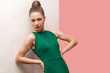 Portrait of serious beautiful young woman with bun hairstyle and makeup in green dress standing with hands on waist and looking at camera, lean on white wall. studio shot, isolated on pink background.