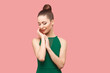 Beauty portrait of happy beautiful young woman with bun hairstyle and makeup in green dress standing with closed eyes, touching her face and smiling. indoor studio shot, isolated on pink background.