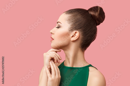Fototapeta Profile side view portrait of calm serious beautiful young woman with bun hairstyle and makeup in green dress standing with closed eyes and touching her chin. studio shot, isolated on pink background. obraz