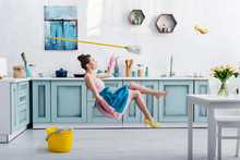Elegant Girl In Apron Levitating With Mop And Yellow Heeled Shoe During House Cleaning In Kitchen