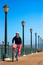 Woman Riding Cruiser Bike On Dock Along The San Francisco Waterfront.