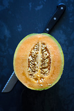 A Halved Tuscan Organic Melon Sits With A Knife On A Dark Background.