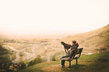 A Man And His Dog Sit On A Bench Overlooking Sunset Of A City.
