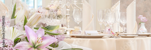 Festive covering table with candlestick and flowers in the foreground Fototapete