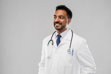 Medicine, Profession And Healthcare Concept - Smiling Indian Male Doctor In White Coat With Stethoscope Over Grey Background