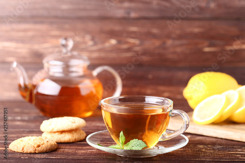 Cup of tea with cookies and mint leafs on wooden table