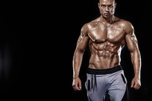 Bodybuilding Competitions On The Scene. Man Sportsmen Physique And Athlete. Black Background With Lights.