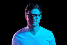 People Concept - Portrait Of Young Man In Glasses And T-shirt Over Ultra Violet Neon Lights In Dark Room