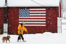 Woman Walking Near American Flag With Her Dog On Snowy Landscape
