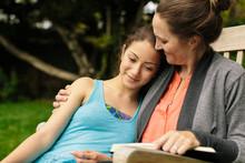 Mom Hugging Teenaged Daughter Outdoors