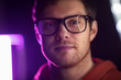 vision, eyewear and people concept - portrait of smiling young man in glasses over ultra violet neon lights in dark room