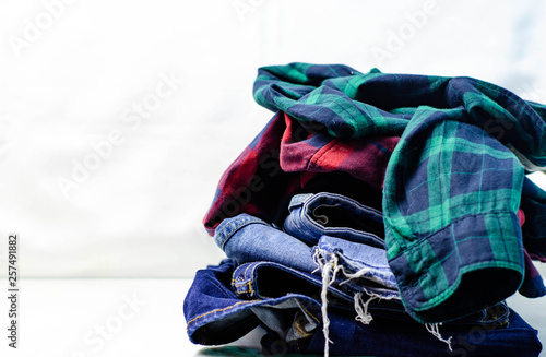 Wall Murals Martial arts Stack of blue jeans and plaid shirts on white background