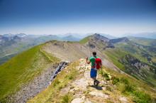 A Solo Male Hiker Descending A Steep Mountain Ridge Near Mont Joly In France, Halfway The Tour Du Mont Blanc.