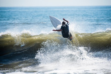 Surfer Riding Wave In Sea