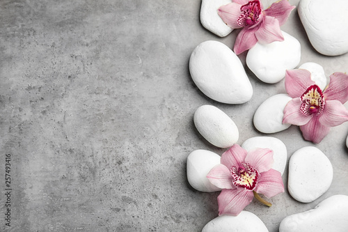 Photo Zen stones and exotic flowers on grey background, top view with space for text