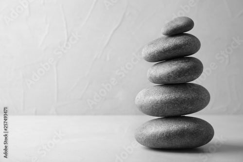 Foto op Plexiglas Stenen in het Zand Stack of zen stones on table against light background. Space for text