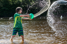 Young Boy Tossing Water From Bucket At Musante Beach.