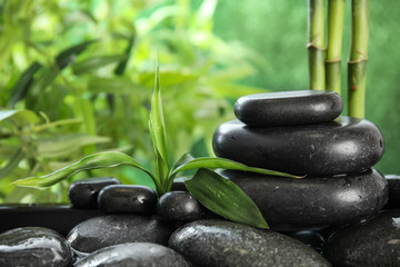 Zen stones and bamboo leaves in water on blurred background. Space for text