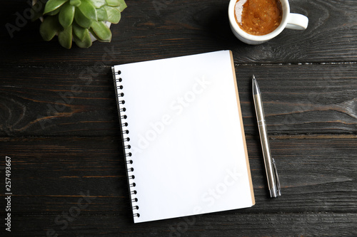 Notebook, coffee and plant on dark wooden background Wallpaper Mural