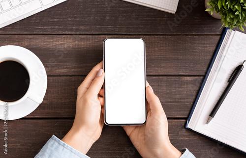 Fototapeta Woman using blank smartphone on workplace desk obraz