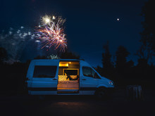 Woman Reading In Van With Fireworks In Background
