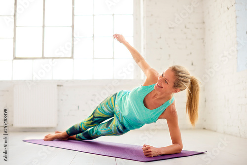 Middle aged woman doing plank exercises in studio