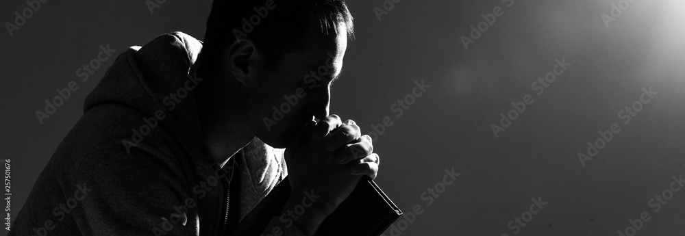 Fototapety, obrazy: Religious young man praying to God on dark background, black and white effect