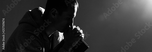 Fototapeta Religious young man praying to God on dark background, black and white effect