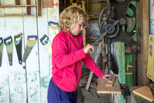A Young Girl Working On A Craft Project In A Camp Woodshop