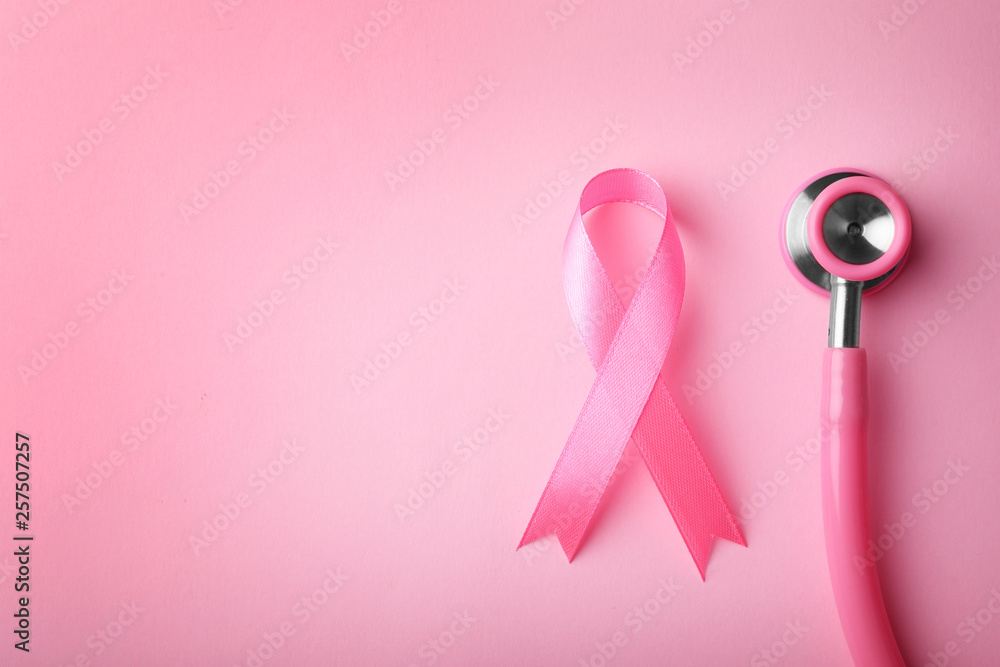 Fototapeta Pink ribbon and stethoscope on color background, top view with space for text. Breast cancer concept