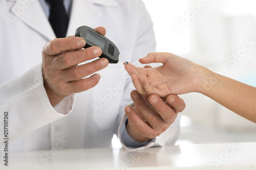 Fotomural  Doctor checking patient's blood sugar level with digital glucometer at table, closeup