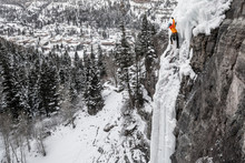 Man Climbing On Frozen Waterfa...