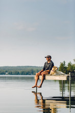 Man And Dog Sitting On The Dock At A Lake.