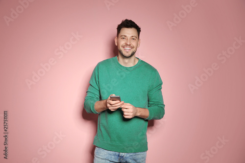 Fotografia  Handsome man with mobile phone on color background