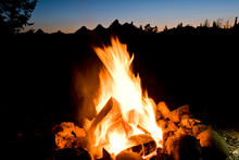 Campfire Burning In Forest Against Silhouetted Mountains In Background